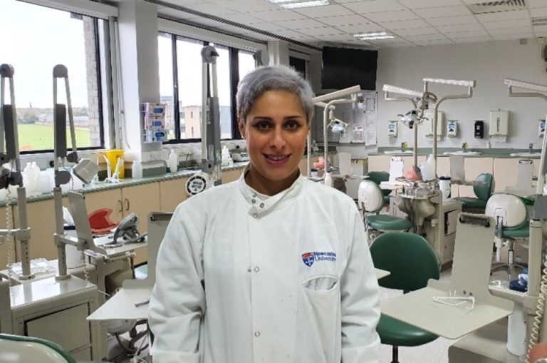 Nadia in white coat stood in dental lab